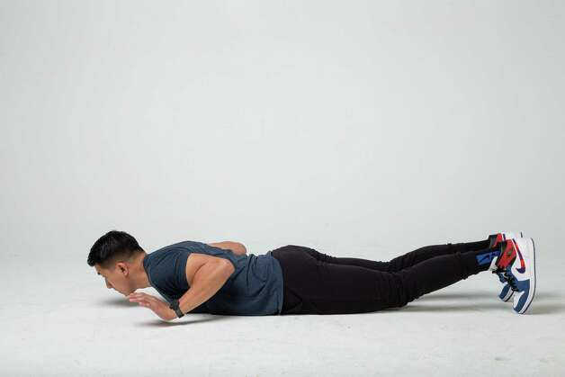 Lower your body down slowly until your stomach is on the ground. Release your hands briefly before pushing back up into the plank position. Photo: Godofredo A. Vásquez, Houston Chronicle / Staff Photographer / © 2021 Houston Chronicle