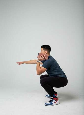 Lower your body into a squat position with your right arm stretched in front of you. Photo: Godofredo A. Vásquez, Houston Chronicle / Staff Photographer / © 2021 Houston Chronicle
