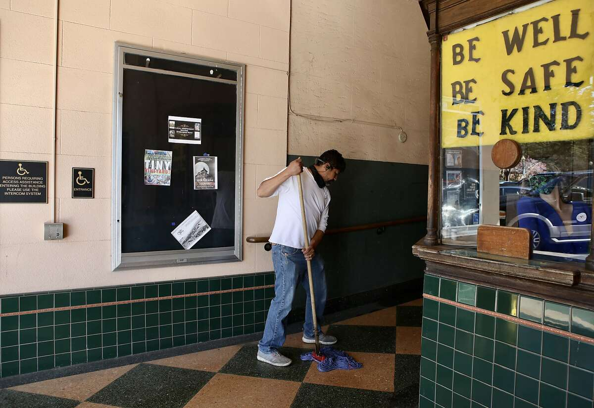 Janitor Francisco Dorate mops the entrance floor at the Sebastiani Theatre in Sonoma Square in March as a sign in the concession booth advises