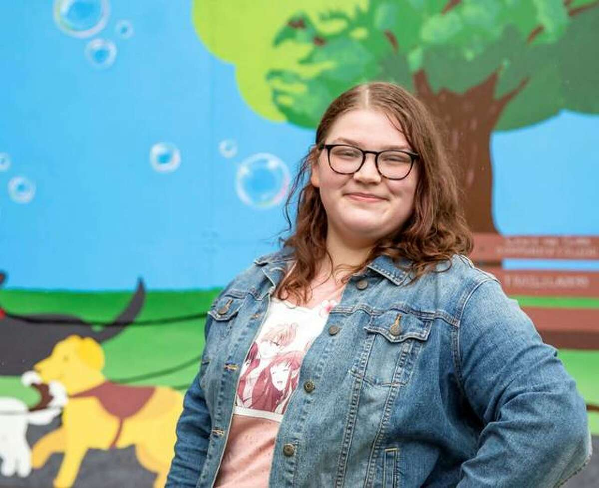 Lewis and Clark Community College graduate Breanna Sak stands in front of the interactive mural she created on campus. This was the first year for the mural contest, which was the brainchild of Professor of Communications Chrissie Chapman.