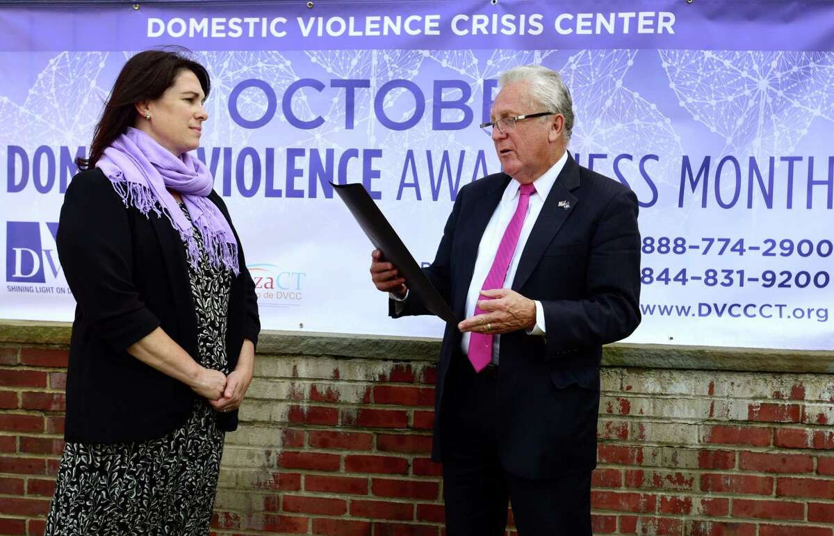 Norwalk Mayor Harry Rilling, right, reads a proclamation to representatives of the Domestic Violence Crisis Center including Executive Director Suzanne Adam, left, and the Norwalk Police Department during a special event Tuesday, October 1, 2019, announcing October as Domestic Violence Awareness Month in front of City Hall in Norwalk, Conn.