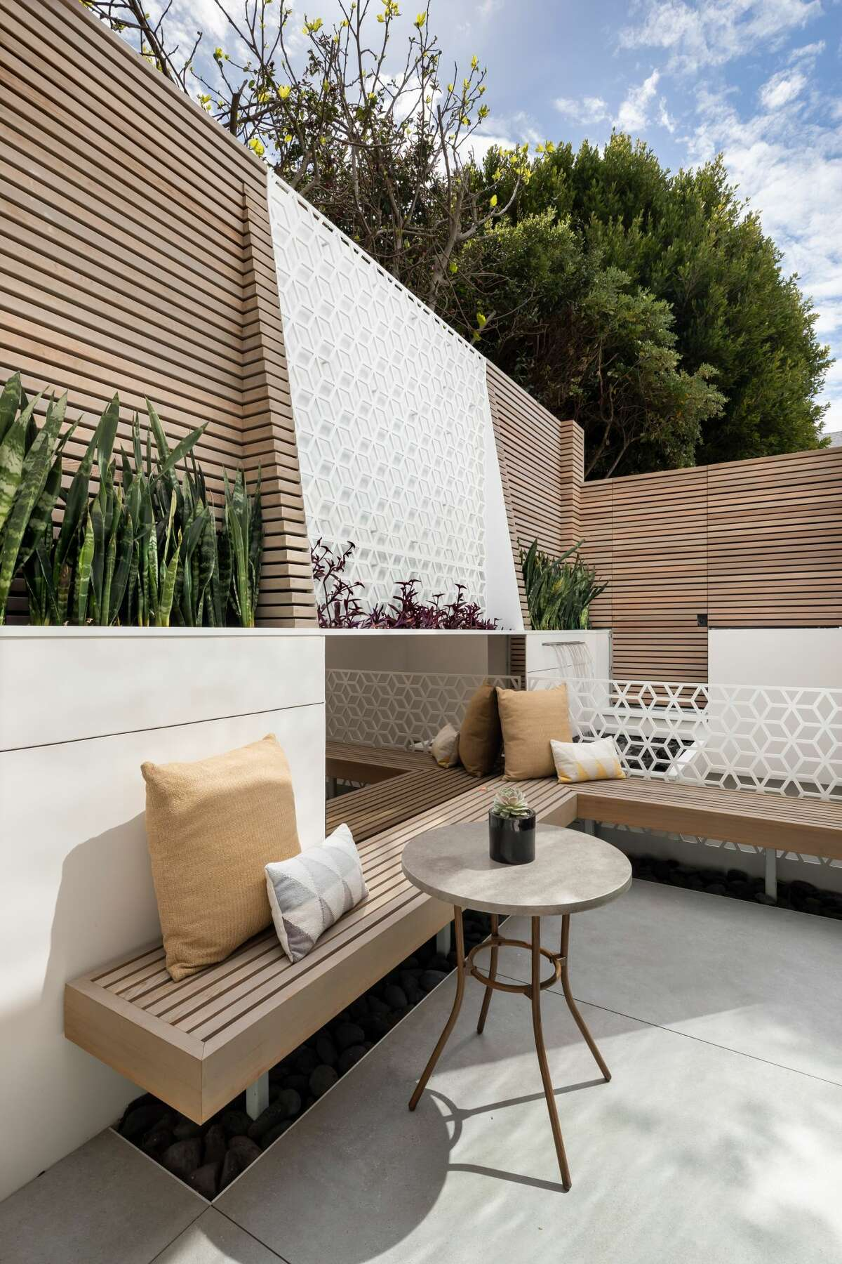 The lower-level patio features lounge seating and an impressive water feature.