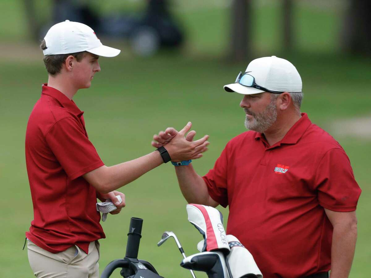 Jake Lile of The Woodlands gets a high-five from head coach Eri Noski after finishing the Class 6A UIL State Golf Championship at Legacy Hills Golf Club, Tuesday, May 18, 2021, in Georgetown.