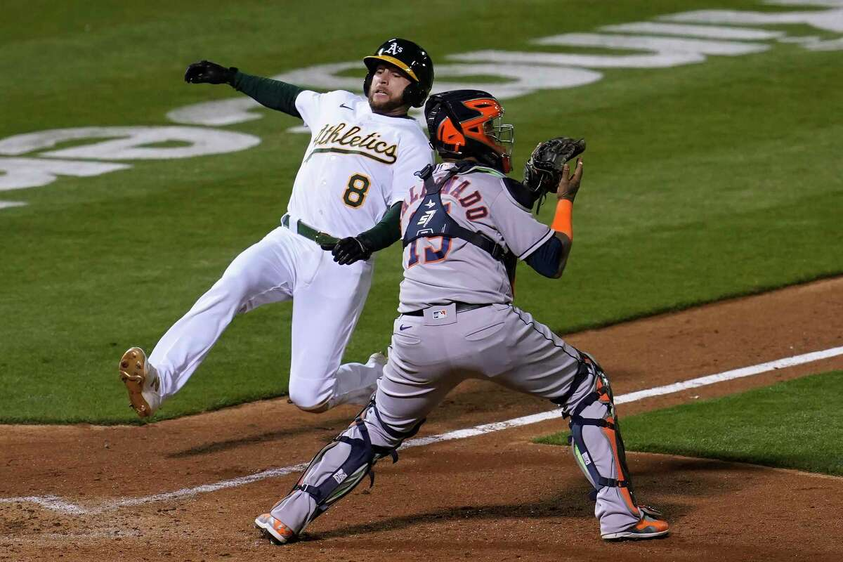 Oakland Athletics' Jed Lowrie, left, slides home to score past Houston Astros catcher Martin Maldonado during the seventh inning of a baseball game in Oakland, Calif., Tuesday, May 18, 2021. (AP Photo/Jeff Chiu)