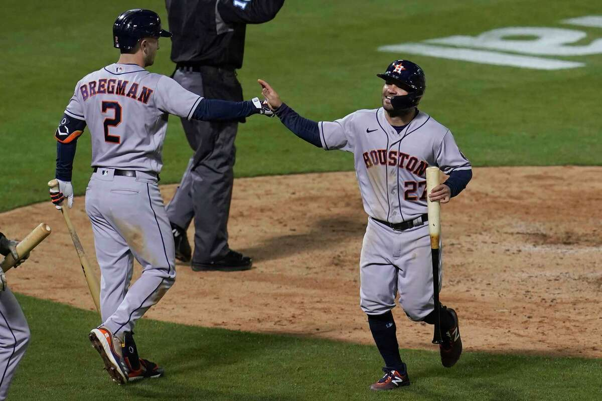 Houston Astros' Jose Altuve, right, is congratulated by Alex Bregman after scoring against the Oakland Athletics during the seventh inning of a baseball game in Oakland, Calif., Tuesday, May 18, 2021. (AP Photo/Jeff Chiu)