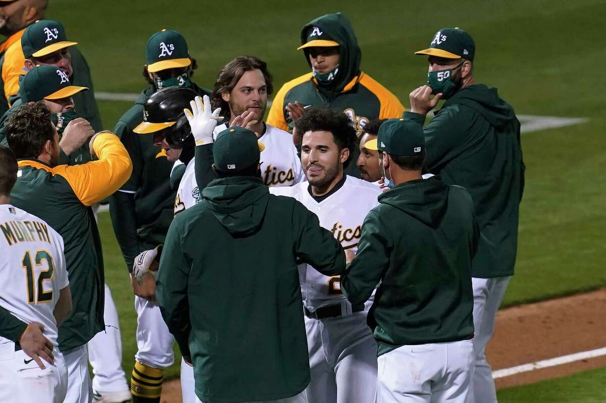 Oakland Athletics' Ramon Laureano, middle right facing, is congratulated by teammates after hitting a sacrifice fly that scored Mark Canha during the ninth inning of a baseball game against the Houston Astros in Oakland, Calif., Tuesday, May 18, 2021. (AP Photo/Jeff Chiu)