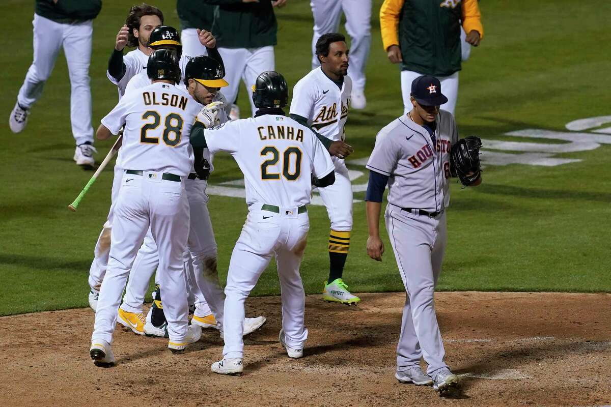 Houston Astros pitcher Bryan Abreu, right, walks away as Oakland Athletics' Ramon Laureano, third from left, is congratulated by teammates after hitting a sacrifice fly that scored Mark Canha (20) during the ninth inning of a baseball game in Oakland, Calif., Tuesday, May 18, 2021. (AP Photo/Jeff Chiu)