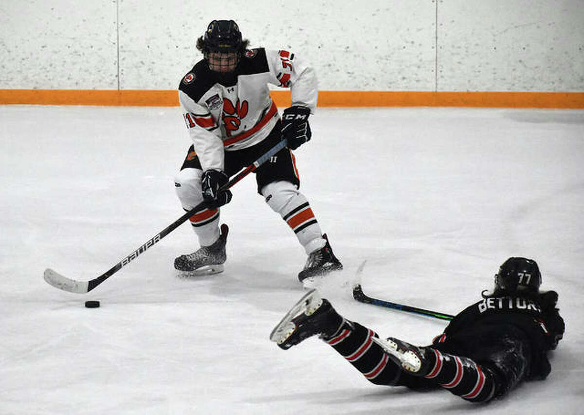 Edwardsville's Anthony Ruklic holds on to the puck as Granite City's Drake Bettorf slides by in the first period of Game 1 of the MVHCA championship on Tuesday inside the East Alton Ice Arena.