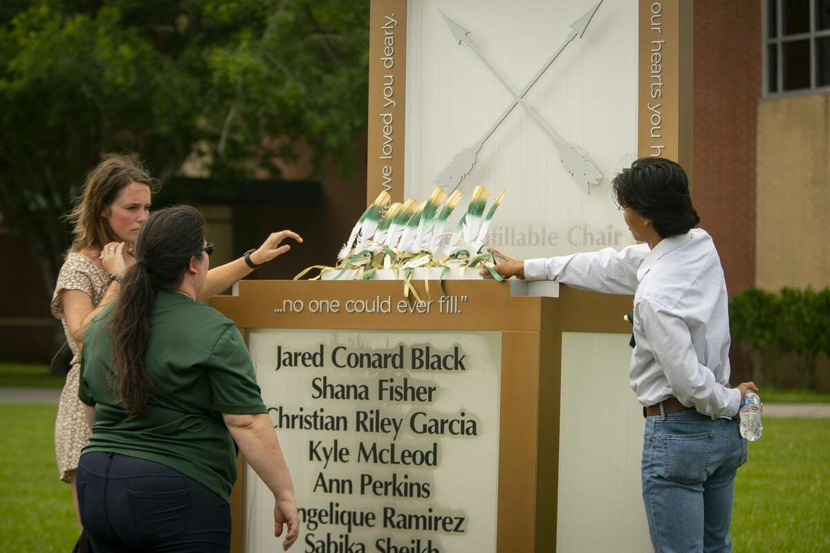 Corrigan Garcia, who graduated from Santa Fe High School in 2018, and Maegan Huddleston, who graduated in 2019, and Megan Grove, who chair's the Santa Fe Ten Memorial Foundation, place ten feathers representing the ten victims of the 2018 Santa Fe school shooting on the new memorial to the ten victims, Tuesday, May 18, 2021, outside of the high school in Santa Fe.