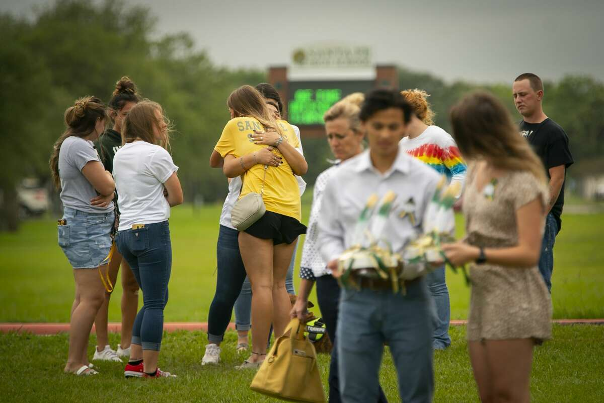 Students hug as they view the new memorial to the ten victims of the 2018 shooting at the high school, following a dedication ceremony, Tuesday, May 18, 2021, outside of the high school in Santa Fe. The Santa Fe Ten Memorial Foundation unveiled the