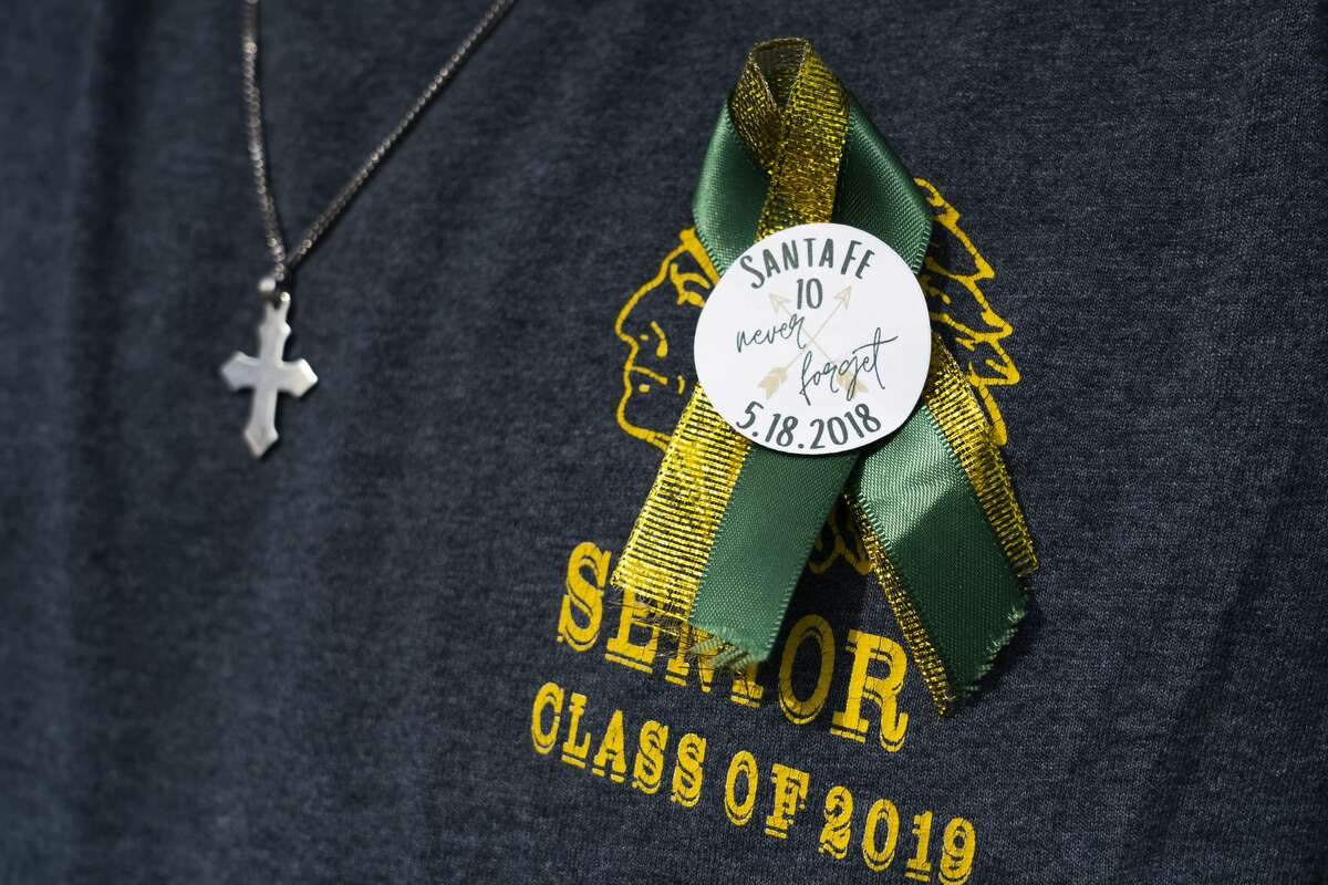 Santa Fe High School alumnus Bailey Link wears a ribbon as he visits the new memorial to the ten victims of the 2018 shooting at the high school, following a dedication ceremony, Tuesday, May 18, 2021, outside of the high school in Santa Fe. The Santa Fe Ten Memorial Foundation unveiled the