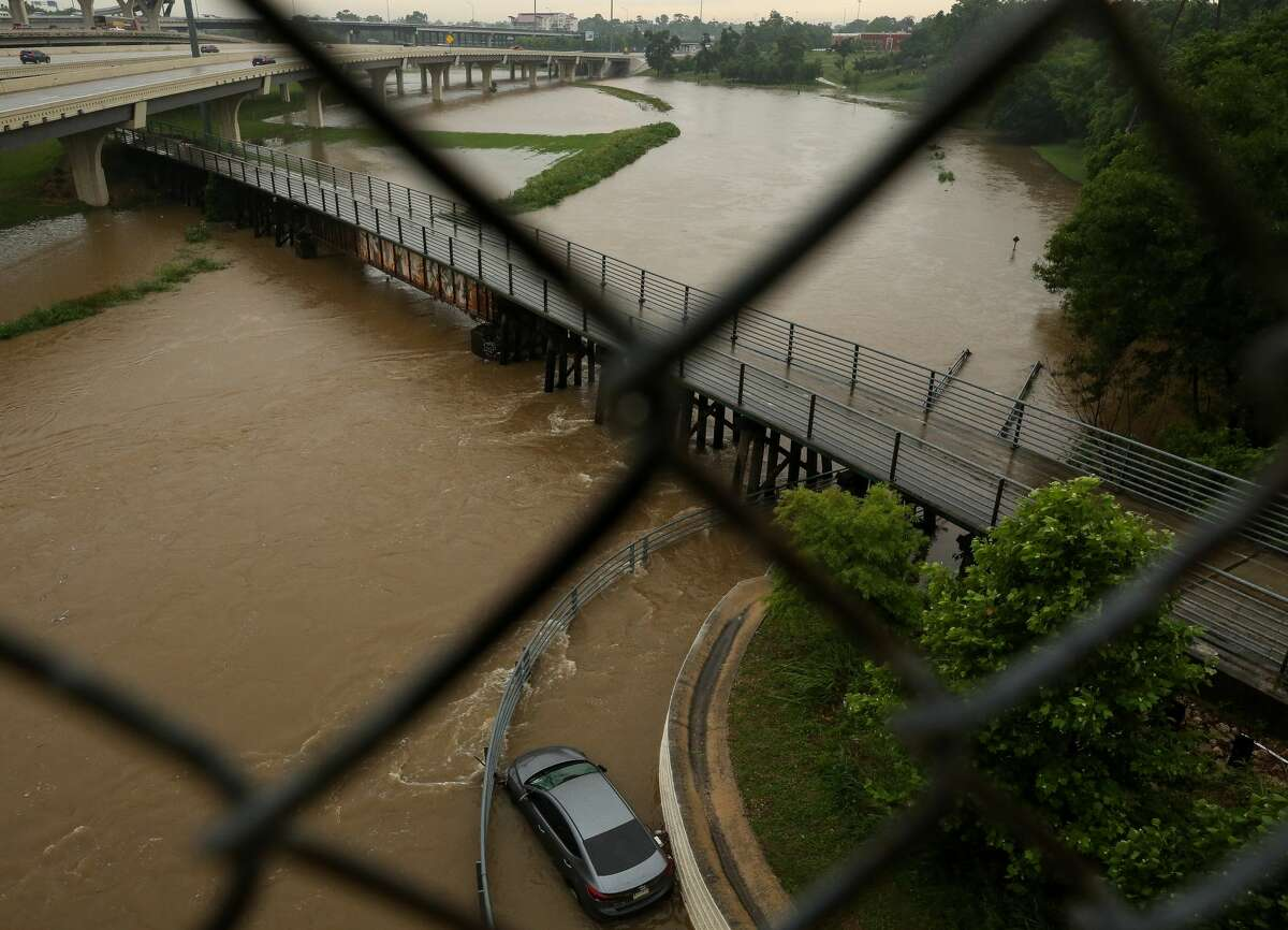 A vehicle can be seen stuck in a flooded bend of White Oak Bayou Greenway Trail, near Hogan Street on Wednesday, May 19, 2021, in Houston.