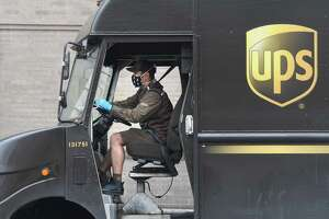 A UPS driver wears a face mask and gloves while making deliveries along Greenwich Avenue in Greenwich, Conn. Tuesday, April 21, 2020.