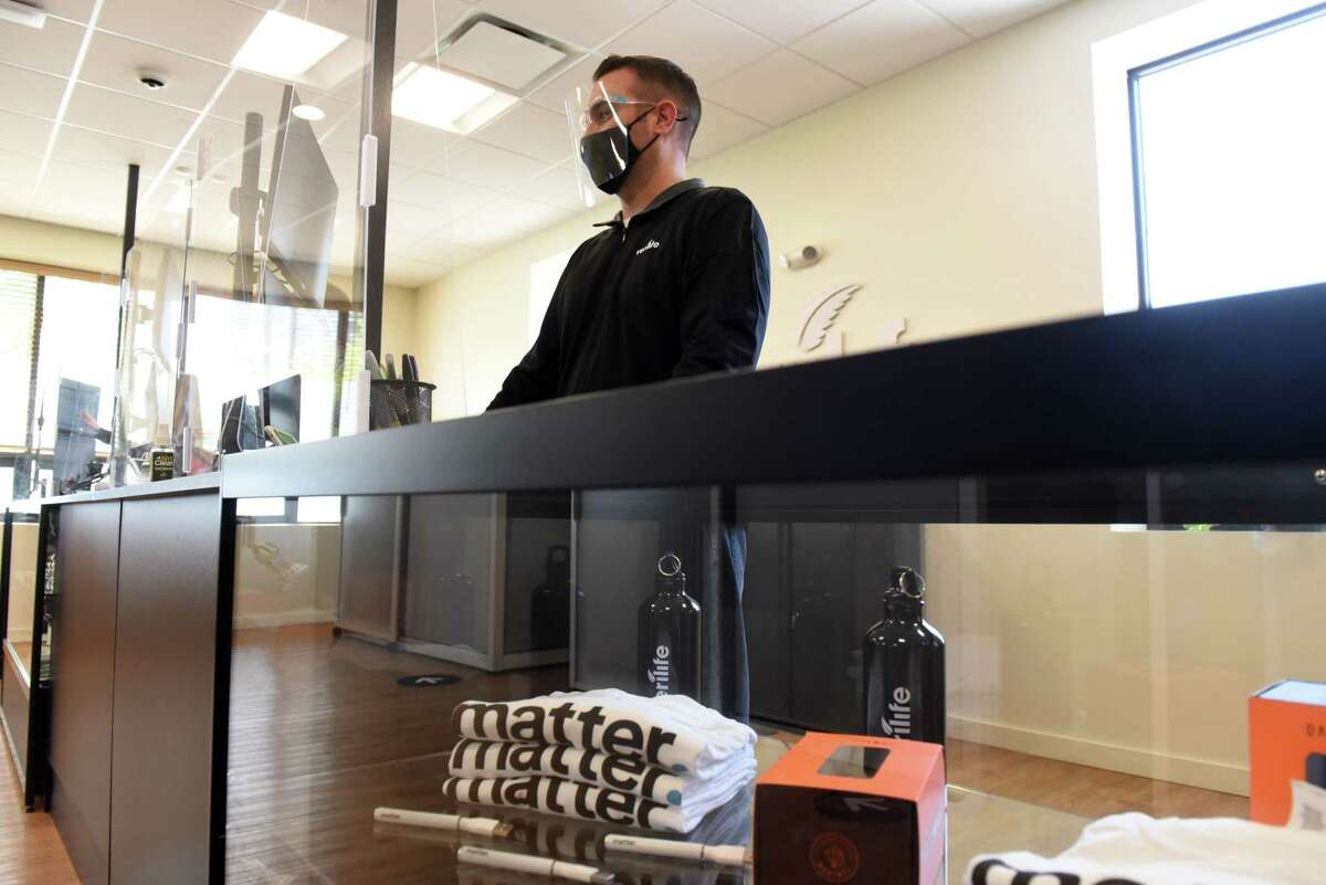 Pharmacist Kevin Harbison works behind the counter in the Verilife cannabis dispensary on Tuesday, May 18, 2021, in Guilderland, N.Y. Modifications to medical cannabis rules which were passed alongside adult-use legalization in March have been slow rollout. (Will Waldron/Times Union)