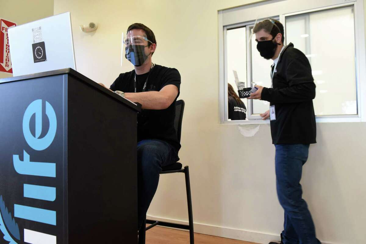 Verilife cannabis dispensary pharmacist Tom Larson, left, works at his station as an oder is dispatched, right, on Tuesday, May 18, 2021, in Guilderland, N.Y. Modifications to medical cannabis rules which were passed alongside adult-use legalization in March have been slow rollout. (Will Waldron/Times Union)