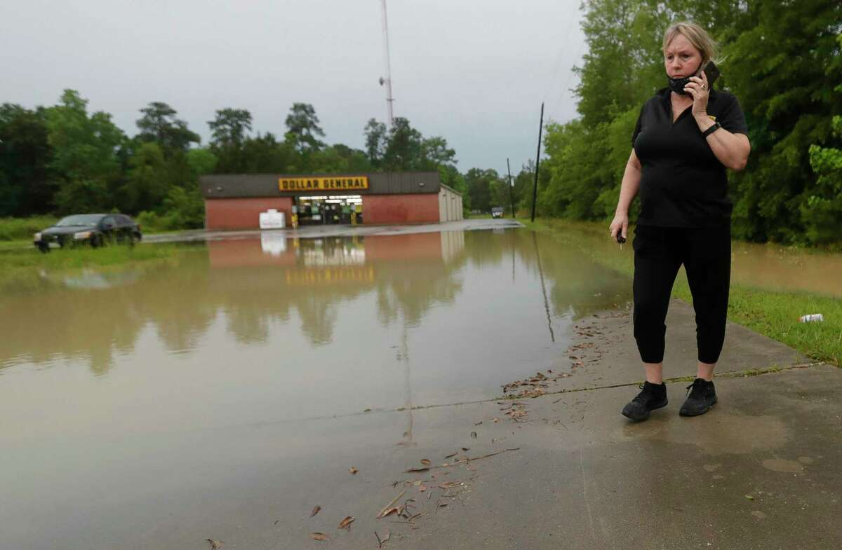"""Jill MacManous talks on the phone to her manager as she tries to get across the parking lot for work at the Dollar General after heavy rain over night, Wednesday, May 19, 2021, in New Caney. """"I'm worried my car won't make it across, but I'm more worried I won't be able to get home,"""" MacManous said. """"If we get enough rain it will come into the store."""""""