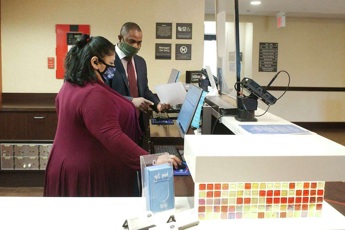 Pearland Hampton Inn General Manager Anuar Castro works with Julie Aguilar at the front desk of the Hampton Inn in Pearland.