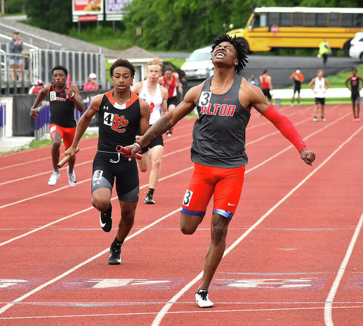 Alton's Marty Boey (right) crosses the finish line to to bring home the Redbirds' victory in the 4x100 relay Tuesday at the Madison County Large-Schools track meet at Collinsville.