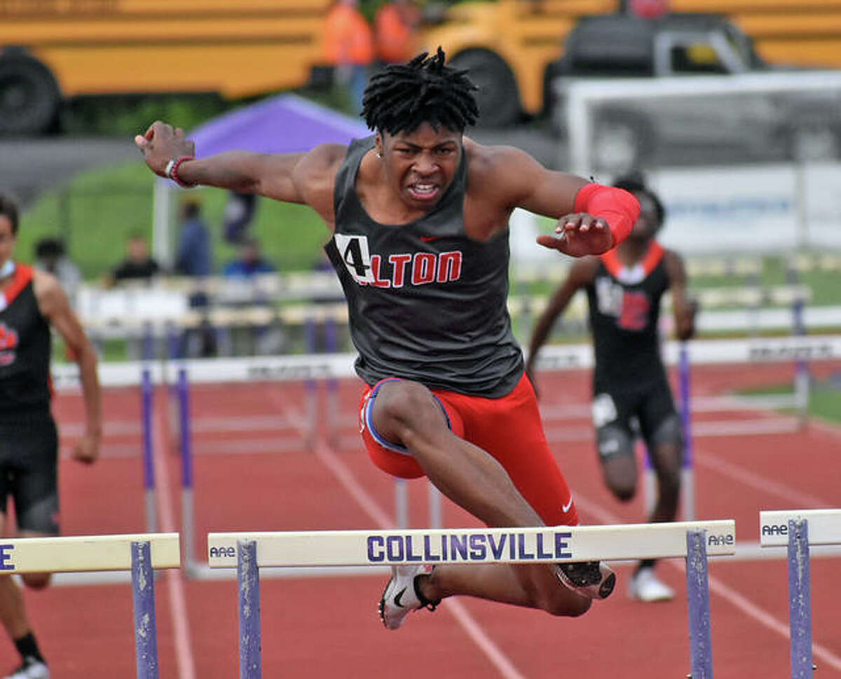 Alton's Marty Boey clips the final hurdle in the 300-meter hurdles on Tuesday at the Madison County Large-Schools track meet at Collinsville. Boey fell face-down to the track, but had a big enough lead to crawl to the finish to win the race.