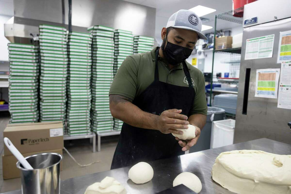 Brian Lee molds pizza dough at Marco's Pizza, Tuesday, May 18, 2021, in Conroe. Brian Lee and his family used to own Donut Wheel, a local donut shop, for over a dozen years.