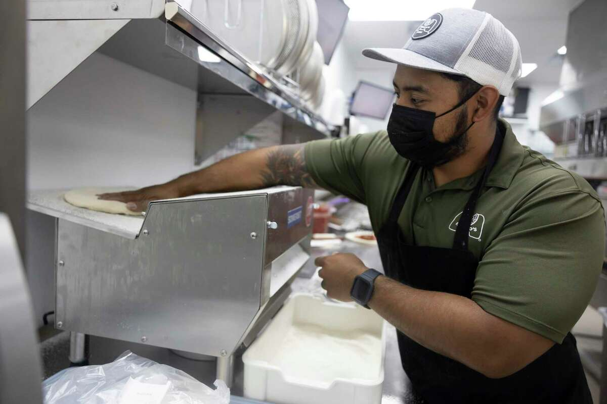 Brian Lee flattens pizza dough at Marco's Pizza, Tuesday, May 18, 2021, in Conroe. Brian Lee and his family used to own Donut Wheel, a local donut shop, for over a dozen years.