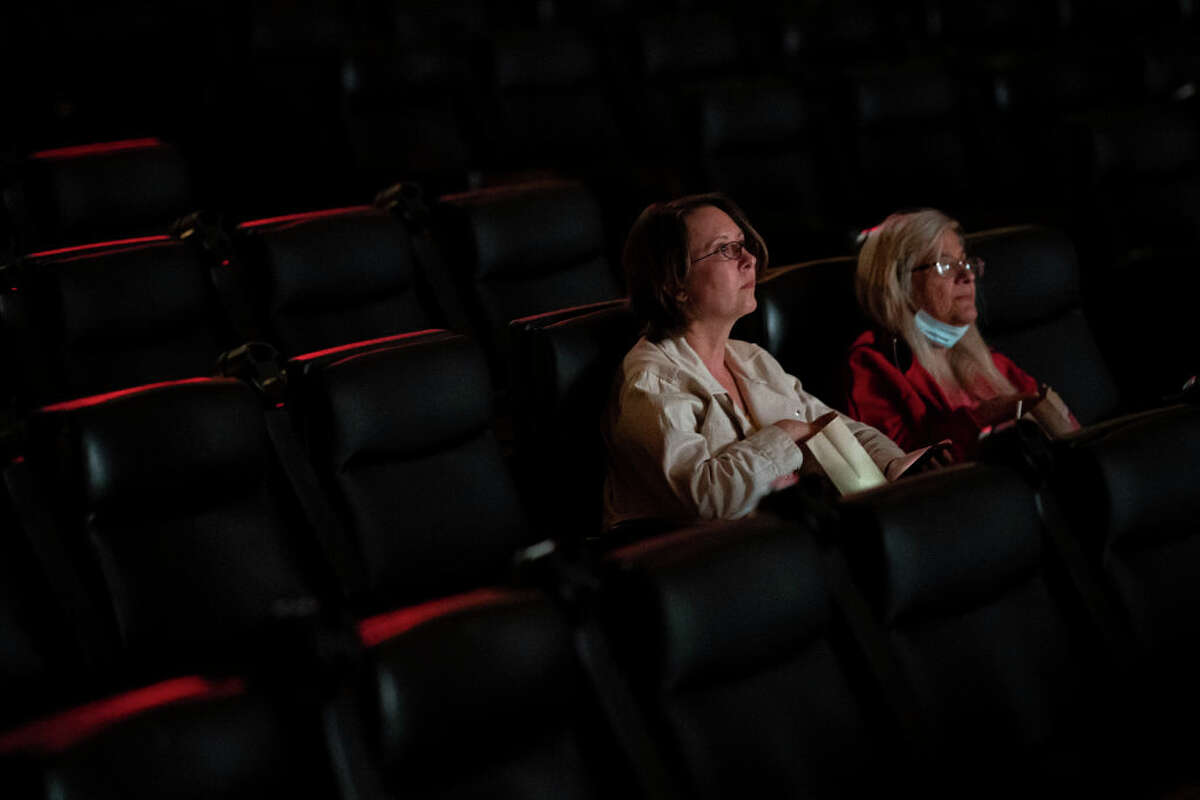 Two moviegoers attend a nearly empty film showing at the Kiggins Theatre on May 14, 2021 in Vancouver, Washington. Gov. Jay Inslee announced Thursday that the state-wide mask mandate would no longer apply to fully vaccinated adults.
