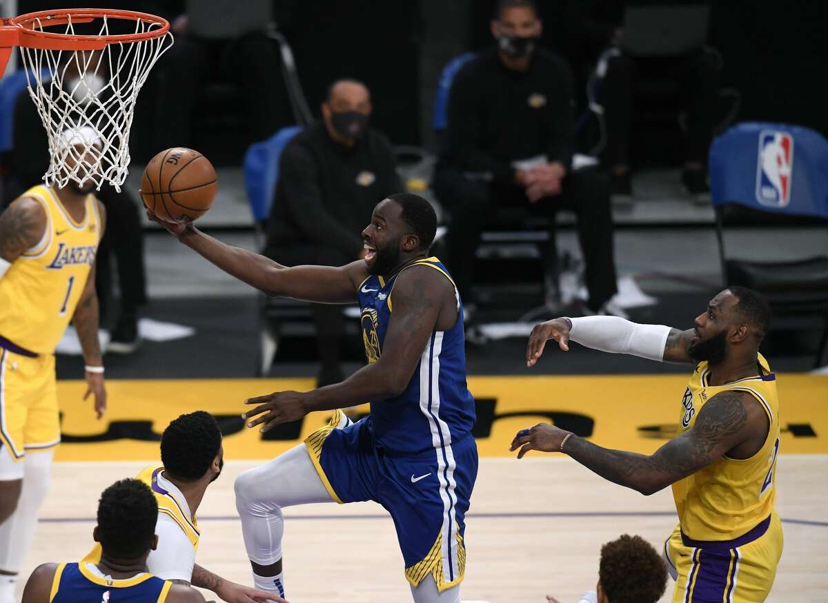 Draymond Green of the Golden State Warriors scores on a layup past LeBron James of the Los Angeles Lakers during a 115-113 Warriors win on January 18, 2021.