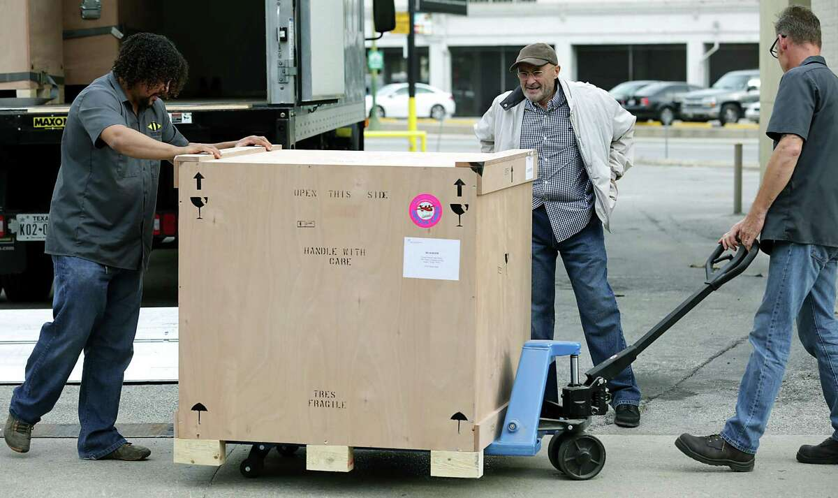 Phil Collins, center, watches the transfer of a crate of containing items from his personal collection that he donated to the Alamo. Tuesday Oct. 28, 2014.