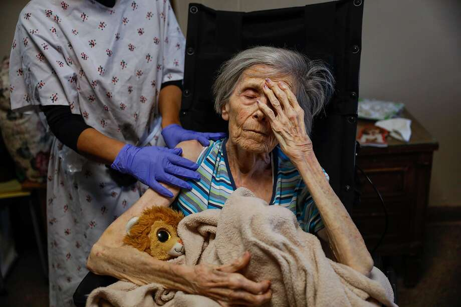 Pat Michelin, 95, puts her hand to her head as she prepares to receive the second dose of her COVID-19 shot at Gordon Manor assisted living facility on Thursday, Feb. 18, 2021 in Redwood City, California. Pat has dementia and the pandemic has caused her to deteriorate quickly. Before the COVID-19 pandemic she could have a conversation with her daughter. Now, she doesn't know who her daughter is. Photo: Gabrielle Lurie/The Chronicle