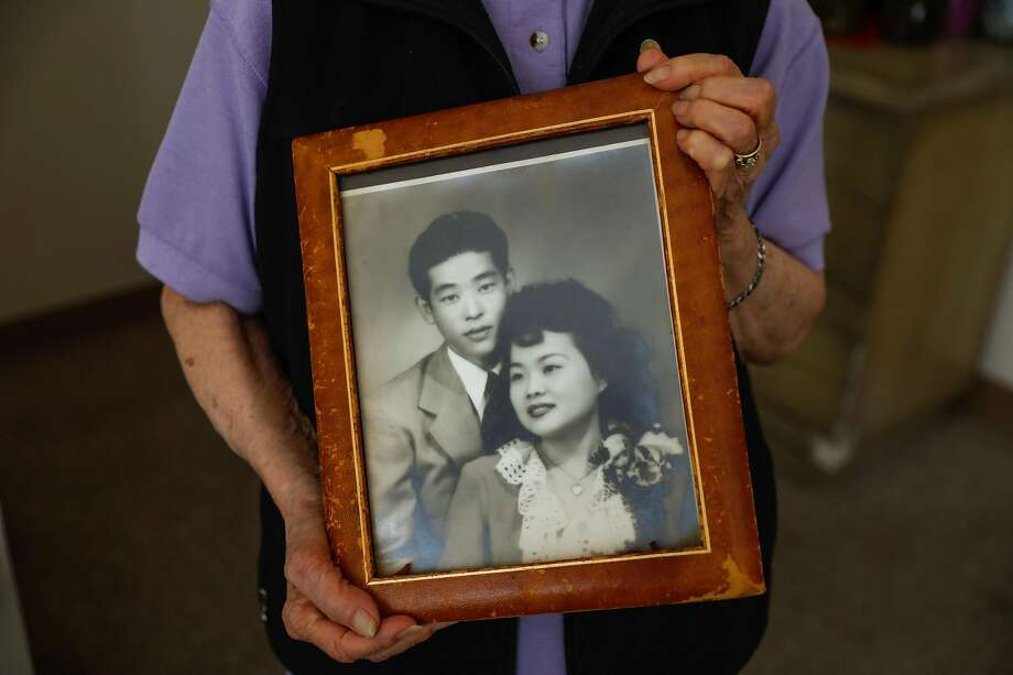 96-year-old Mildred Hamada shows off an old photograph of her with her husband Wallace Hamada who died a few years ago at Gordon Manor assisted living facility on Thursday, April 29, 2021 in Redwood City, California. Mildred began living at Gordon Manor because her husband had dementia but she too developed memory loss as the years went on. During the pandemic Mildred's family removed her from the facility to keep her safe. At home with her family Mildred became extremely depressed and cried regularly. She did not like leaving the assisted living facility where she had lived for many years with her husband before he died. When she was able to back to the facility she snapped back to being her normal jovial self. Photo: Gabrielle Lurie/The Chronicle