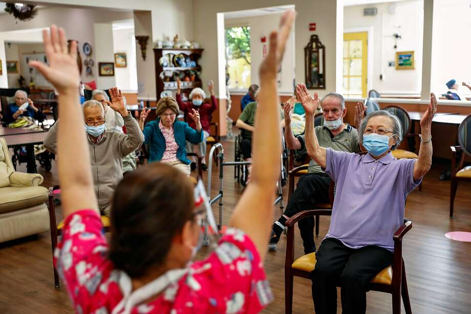 96-year-old Mildred Hamada follows along as caregiver Lani Torres (left) teaches the morning exercise class at Gordon Manor assisted living facility on Thursday, April 29, 2021 in Redwood City, California. Mildred began living at Gordon Manor because her husband had dementia but she too developed memory loss as the years went on. During the pandemic Mildred's family removed her from the facility to keep her safe. At home with her family Mildred became extremely depressed and cried regularly. She did not like leaving the assisted living facility where she had lived for many years with her husband before he died. When she was able to back to the facility she snapped back to being her normal jovial self. Photo: Gabrielle Lurie/The Chronicle