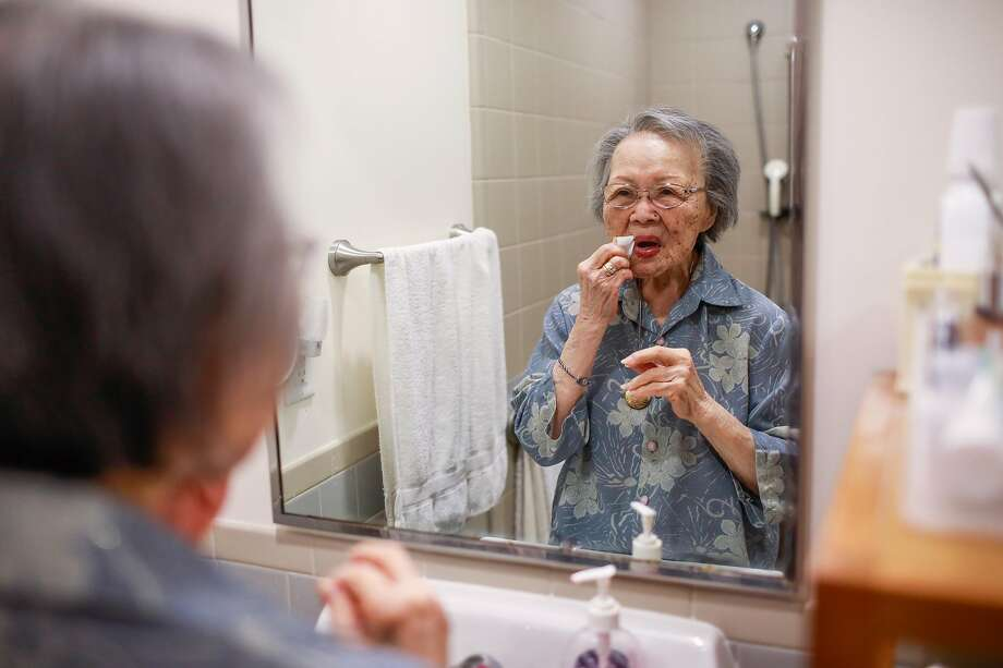 96-year-old Mildred Hamada adjusts her makeup as she gets ready in the morning at Gordon Manor assisted living facility on Friday May 7, 2021 in Redwood City, California. Mildred began living at Gordon Manor because her husband had dementia but she too developed memory loss as the years went on. During the pandemic Mildred's family removed her from the facility to keep her safe. At home with her family Mildred became extremely depressed and cried regularly. She did not like leaving the assisted living facility where she had lived for many years with her husband before he died. When she was able to back to the facility she snapped back to being her normal jovial self. Photo: Gabrielle Lurie/The Chronicle