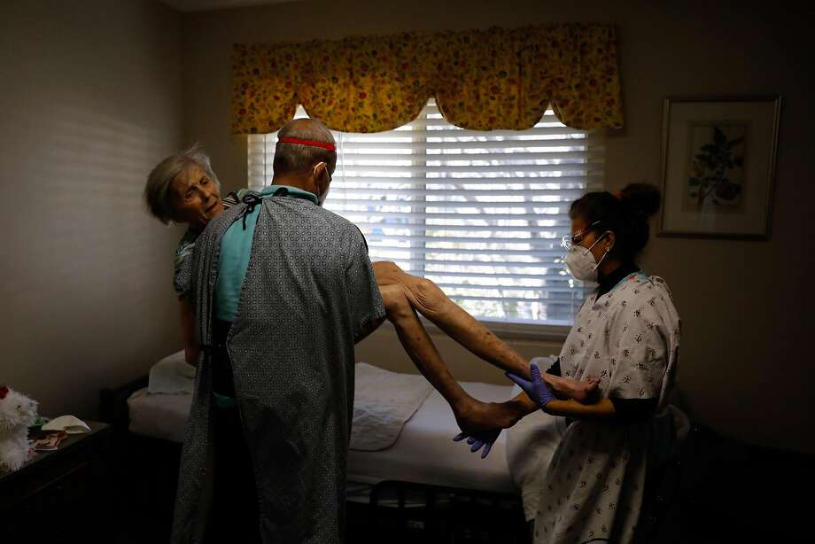 on Thursday, Feb. 18, 2021 in ,Caregivers Jose Rodriguez (left) and Nancy Rubio Campos (right) lift Pat Michelin, 95, out of her wheelchair and back into her bed after receiving the second dose of her COVID-19 shot at Gordon Manor assisted living facility on Thursday, Feb. 18, 2021 in Redwood City, California. Pat requires a lot of assistance because she broke her hip and can no longer walk. She also suffers from dementia which has worsened due to the pandemic. Before the COVID-19 pandemic she could have a conversation with her daughter. Now, she doesn't know who her daughter is. Photo: Gabrielle Lurie/The Chronicle