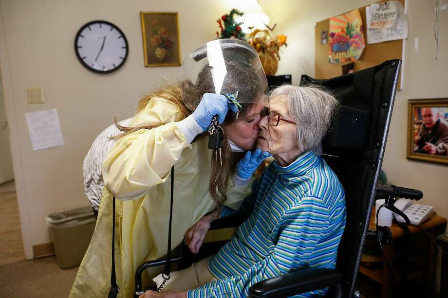 """Sue Ann Michelin gives her mother Pat Michelin (right) a kiss goodbye after one of her firsts visits back since the pandemic at Gordon Manor assisted living facility on Saturday, Feb. 20, 2021 in Redwood City, California. Sue Ann sat across from her for nearly an hour showing her pictures and trying to jog her memory. While fighting back tears she said, """"Mama its me Sue Ann your daughter. Mama, I love you. I love you mama"""". Pat has dementia and the pandemic has caused her to deteriorate. Before the pandemic she could have a conversation with her daughter. Now, she doesn't know who her daughter is. Photo: Gabrielle Lurie/The Chronicle"""