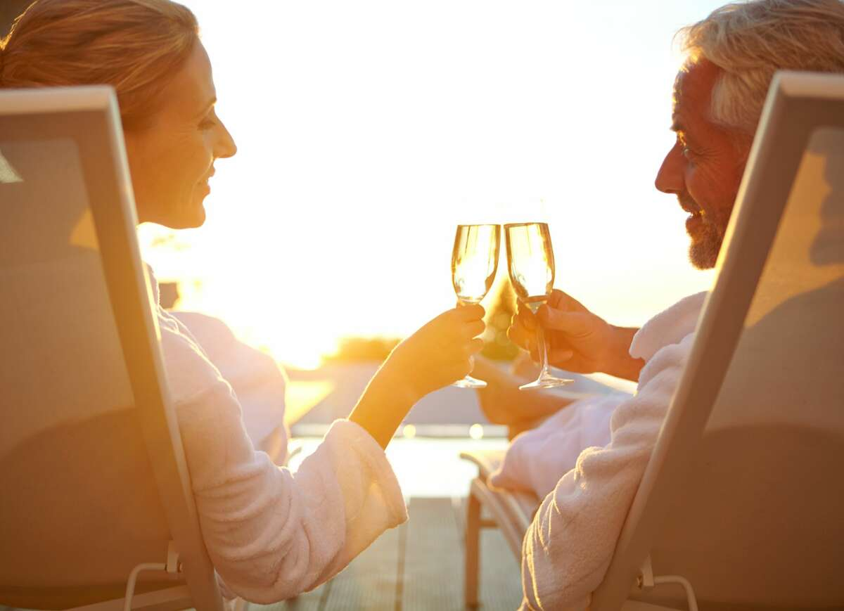 Couple drinking champagne while relaxing in deck chairs at sunset