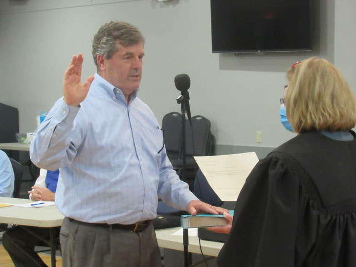 Rick Lauschke is sworn in Tuesday night as a village trustee in Godfrey.