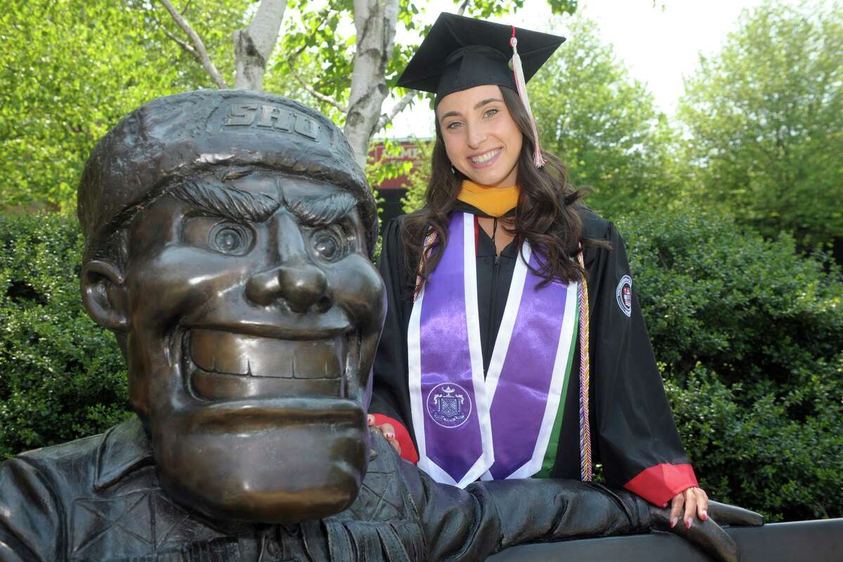 Nursing student Arianna Heonis poses next to a statue of school mascot Big Red, prior to her commencement at Sacred Heart University, in Fairfield, Conn. May 19, 2021.