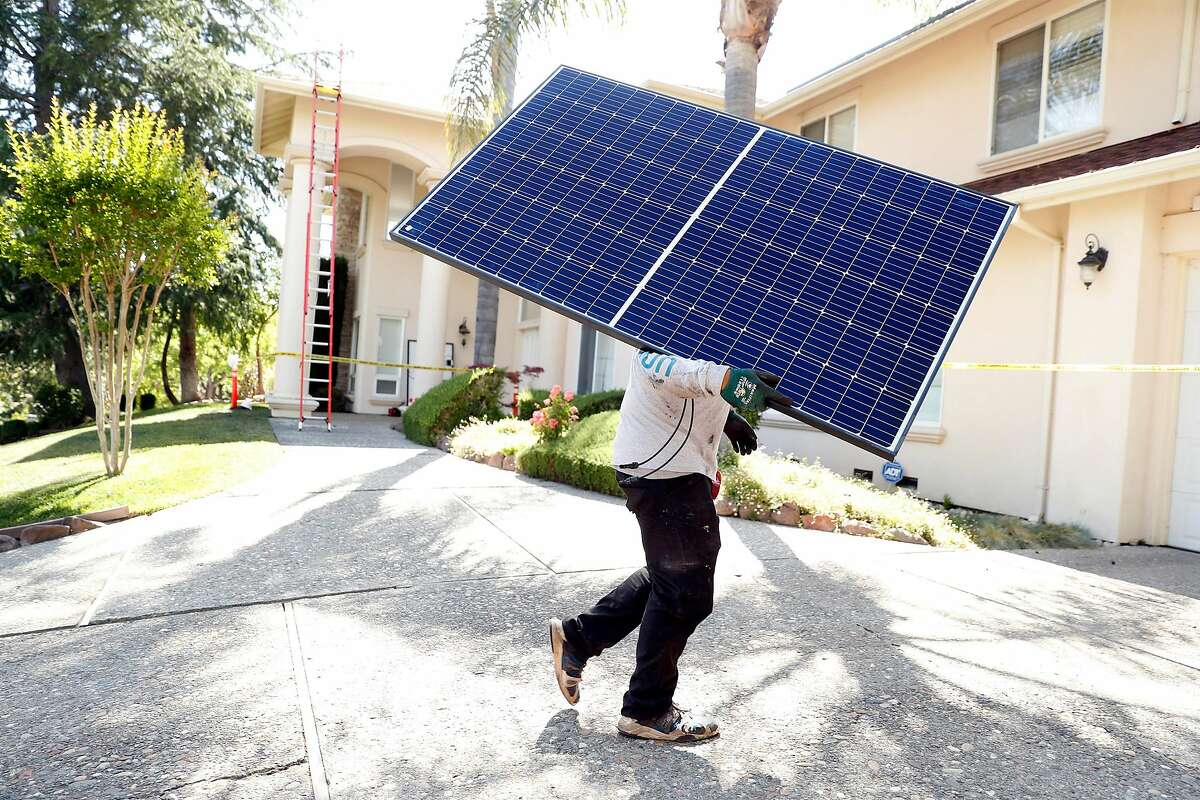 Sunrun employee Gonzalo Najera carries a solar panel before installation at a home in Alamo.