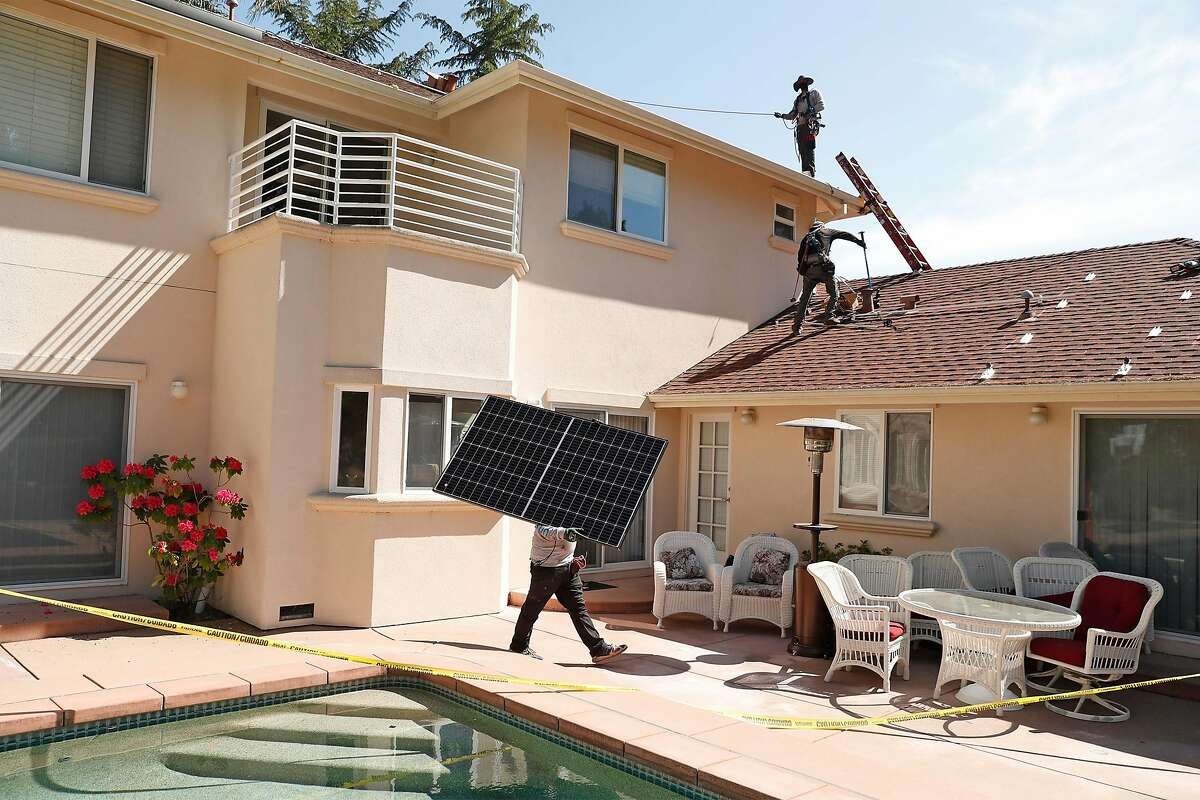 Sunrun employee Gonzalo Najera carries a solar panel before installation at a home in Alamo, Calif., on Monday, May 17, 2021.