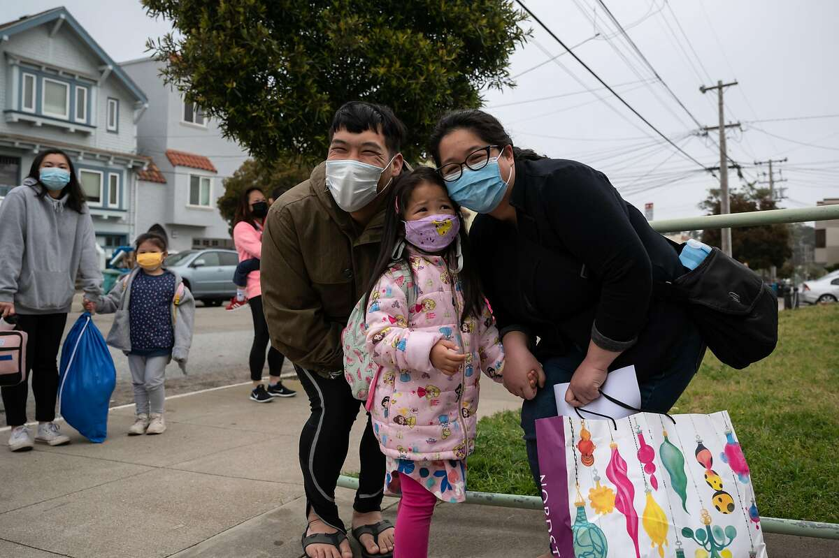 William Luong (L) and Joanna Luong (R) drop off their daughter Evelyn (4) (M) for her first day of school at Jefferson Early Education School. San Francisco, California. April 12, 2021.