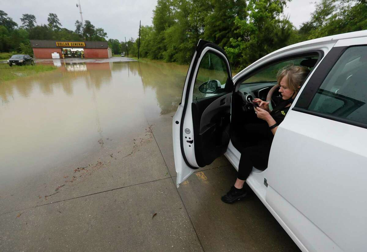 Jill MacManous checks the weather radar for incoming rain as she tries to get across the parking lot for work at the Dollar General following heavy rain over night, Wednesday, May 19, 2021, in New Caney.