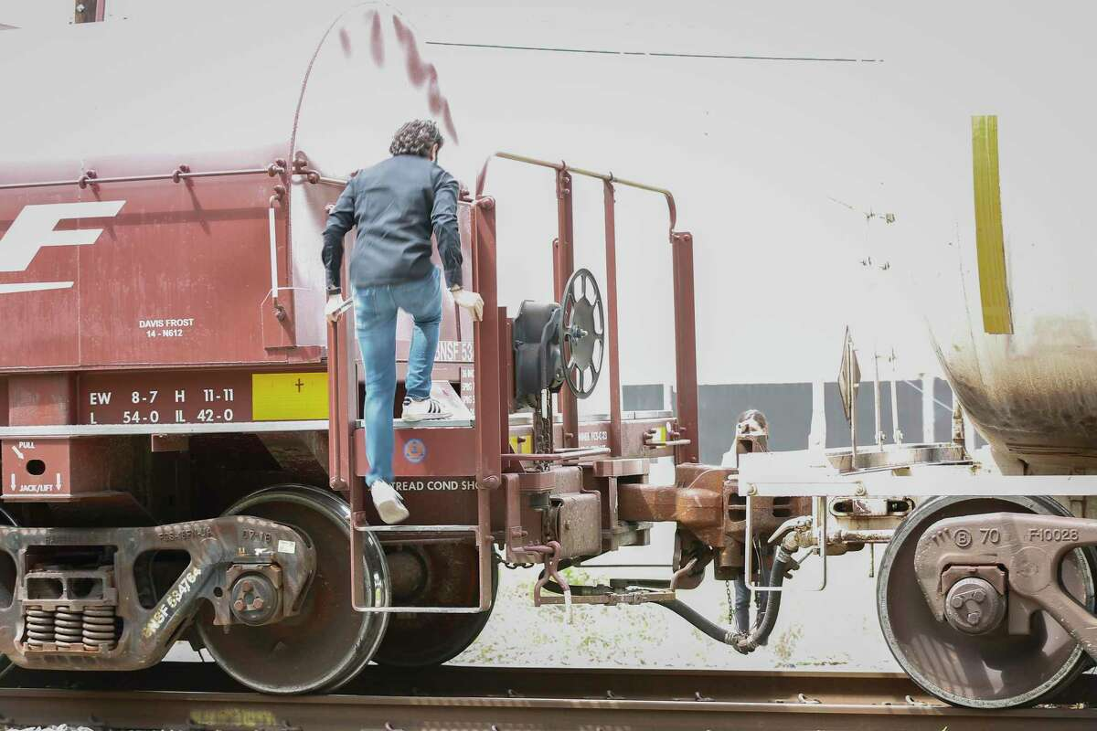 Pedestrians climb over railroad cars after a train stopped for more than 45 minutes on the tracks across Lockwood Avenue on May 18, 2021, in Houston.