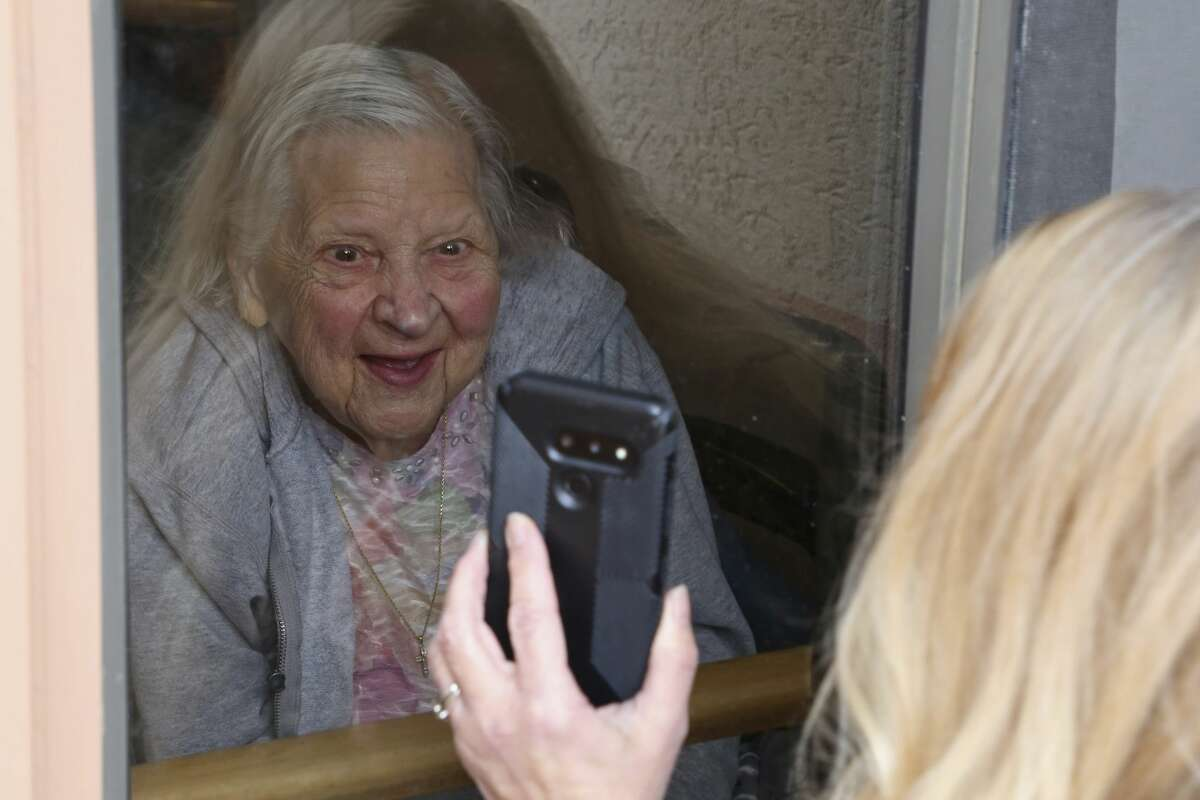 Laura Coriddi shows a photo on her phone through a window to her mother Emma Sahl at Northgate Healthcare facility Saturday, March. 6, 2021, in North Tonawanda N.Y. High rates of COVID-19 throughout New York have left the majority of its nursing homes closed for most indoor visits despite relaxed guidance meant to help open them up for visitors. (AP Photo/Jeffrey T. Barnes)