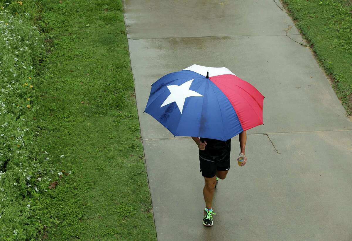 A man uses a Texas-flag umbrella to shield from the rain while walking at Buffalo Bayou Park on Wednesday, May 19, 2021, in Houston.
