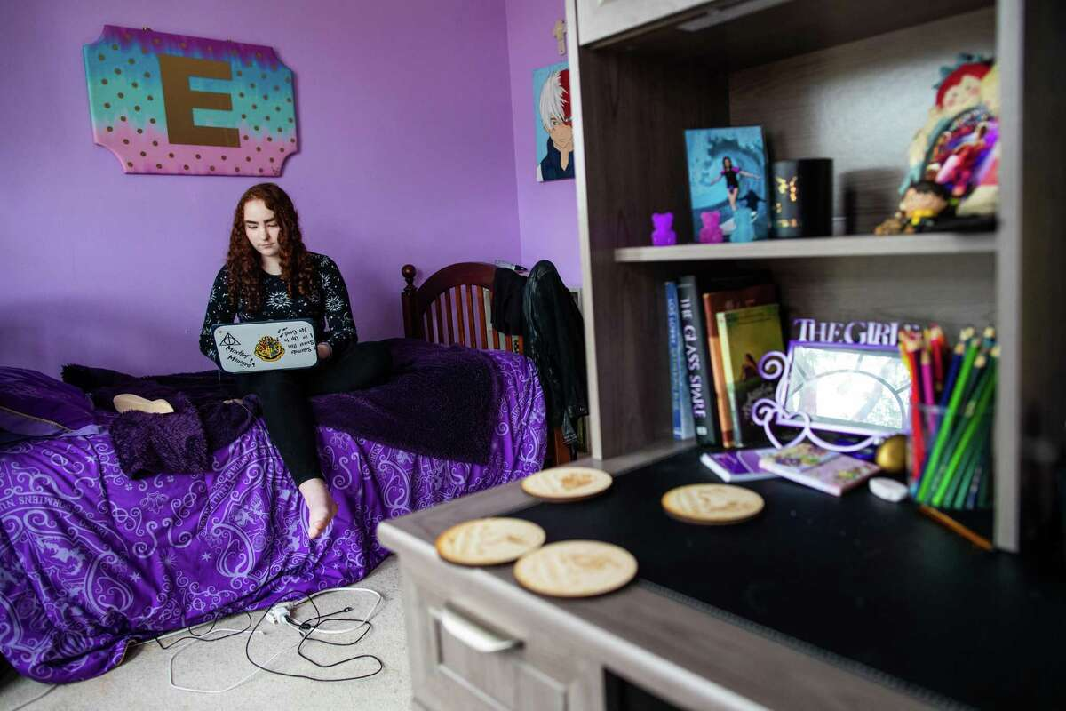 Beck Junior High School's eighth-grader Ellen Holden seats on her bed with her laptop for a portrait at her home, Thursday, April 15, 2021, in Katie. Holden hopes to spend her high school freshman year in virtual instruction. Ellen, 14, said she enjoys the quiet of online classes at home, free from classroom distractions and the social pressures of school.