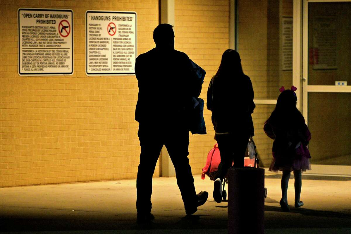 A family walks past signage barring the possesion of concealed and openly carried handguns Feb. 10, 2018, at the YMCA in Midland, Texas. James Durbin/Reporter-Telegram