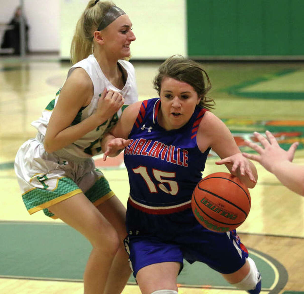 Carlinville's Gracie Reels (15) drives on Southwestern's Morgan Durham in during a 2020 basketball game.