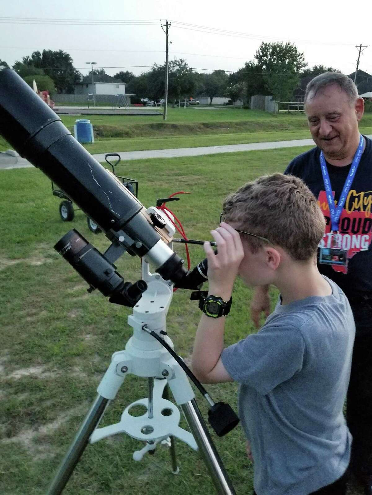 A young stargazer peers through a telescope at a 2019 session of League City's Astronomy in the Park as Dan Roy looks on. Roy and his wife Rebeca will host the monthly program again starting June 5 at Rustic Oaks Park, 5101 Orange Blossom.