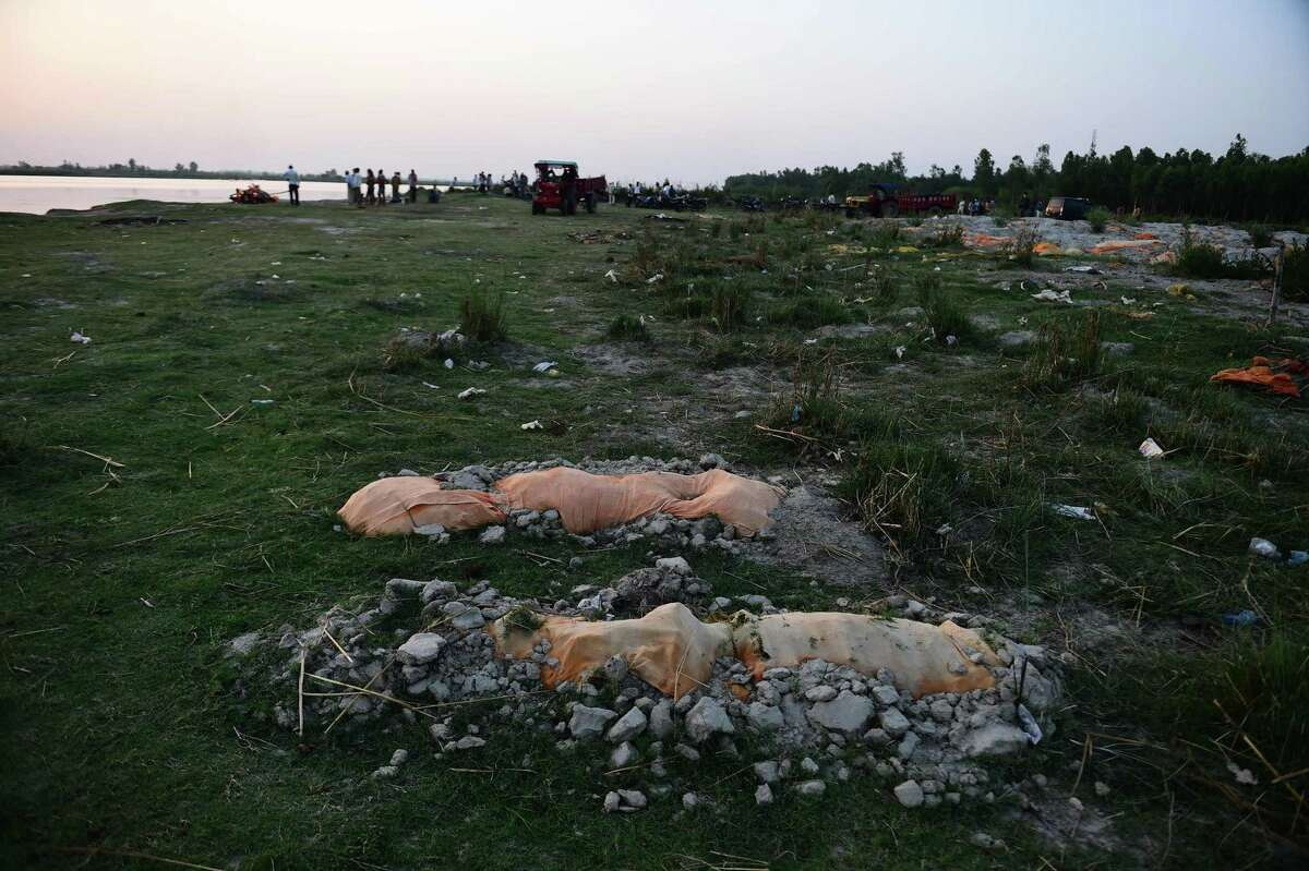 The bodies of people who may have died from COVID-19 are partially buried in the sand near a cremation ground on the banks of Ganges River in Rautapur Ganga Ghat, India, last week.