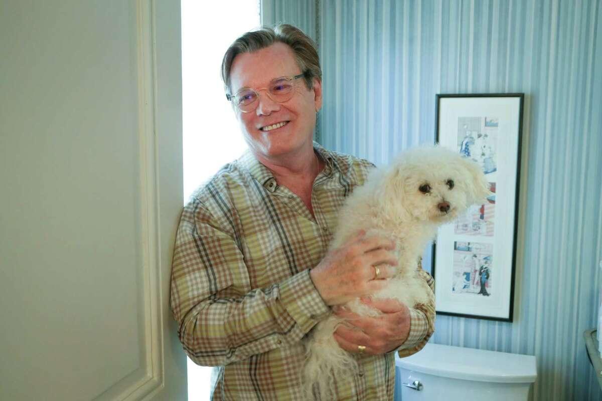 Retired interior designer Dennis McNabb holds his Bolognese dog, Skeeter, at his Galvesto home.